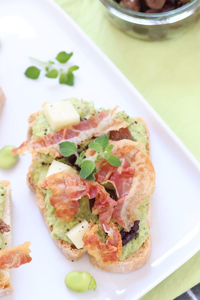 Crostini con crema di fave, olive e pancetta croccante